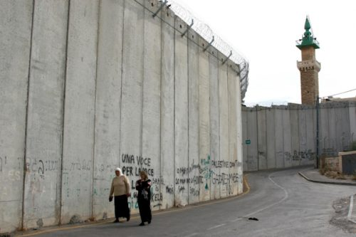 Two Palestinian women walk next to the separation wall in the West bank village of Abu Dis, November 19, 2007. Photo by Anna Kaplan/Flash90.