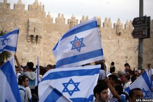"""Ultra-nationalist Israelis wave their national flags during the """"flag march"""" through Damascus Gate in east Jerusalem on May 28, 2014 as the country celebrates the anniversary of its capture in the 1967 Six-Day War. Fearing clashes, police closed the flashpoint Al-Aqsa mosque compound to visitors and in Jerusalem Day speeches Prime Minister Benjamin Netanyahu pledged to never allow the city to be divided. Photo by Saeed Qaq"""